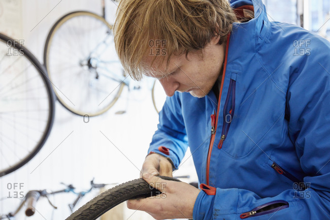 A young man repairing a bicycle