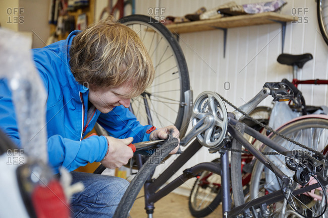 A young man repairing a bicycle in a shop
