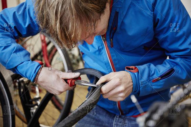 A young man repairing a bicycle in a bike shop