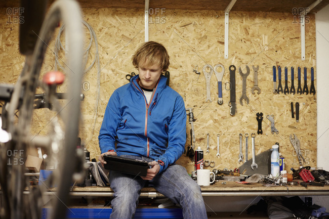 A young man using a digital tablet in his bike shop