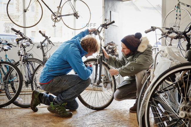 Man checking customer's bike in repair shop