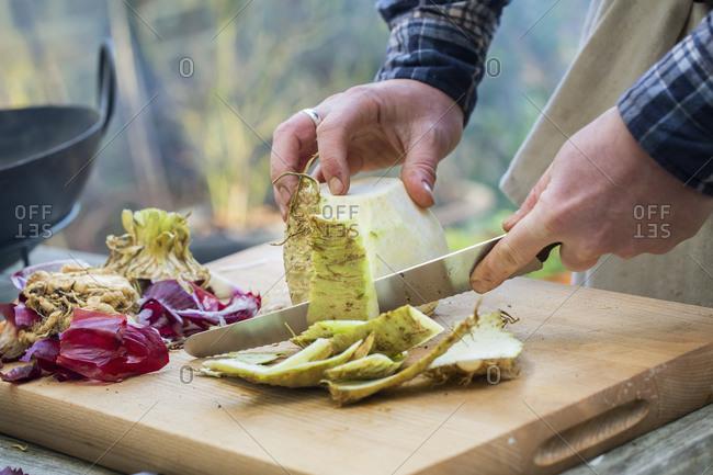 A man chopping vegetables on a board with a knife, peeling celeriac