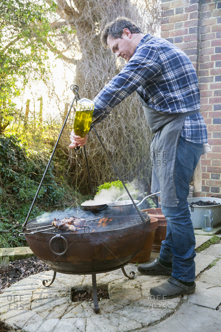 A man cooking roasting game birds over an open fire, pouring olive oil from a bottle on the meat
