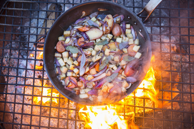 Game birds in a pan surrounded by mirepoix of vegetables above a glowing fire