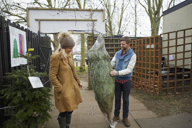 A member of staff carrying a Christmas tree talking to a woman client