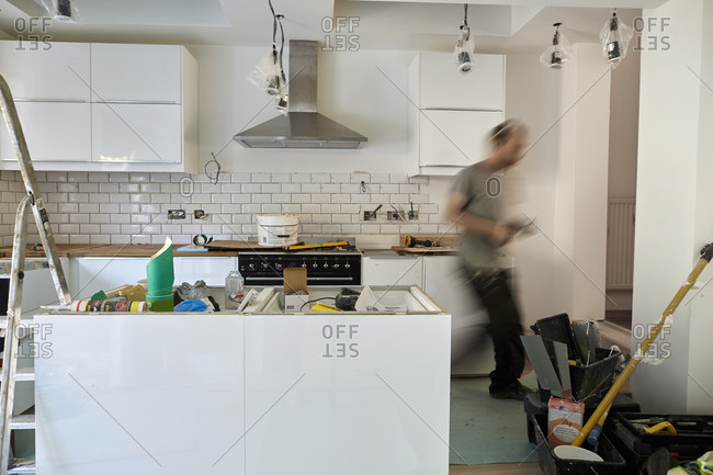 A man working in a kitchen, installing new units