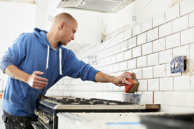 A man finishing tile worker behind stove