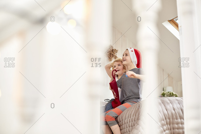 Two children, a boy and girl seen through a bedroom doorway, looking up excitedly, waking up on Christmas morning