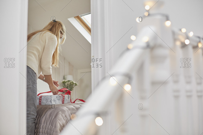 A woman wrapping red ribbons around Christmas presents on a bed, view through the bedroom door