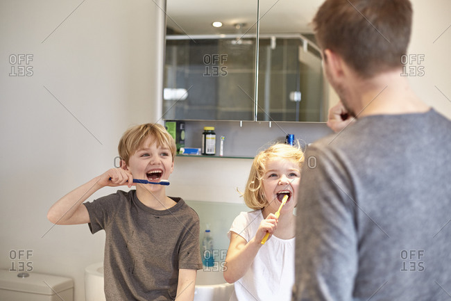 Two children and an adult man cleaning their teeth with toothbrushes in a bathroom