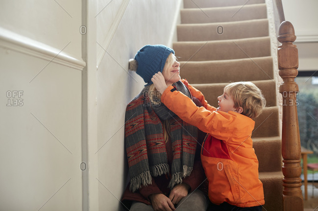 A boy pulling a hat over his mother's eyes