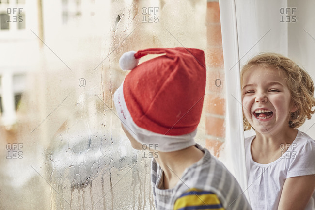 Christmas morning in a family home a boy in a Santa hat looking out of a bedroom window and his sister laughing beside him