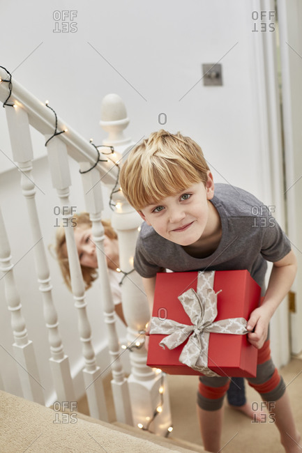 Christmas morning in a family home with two children on the stairs carrying presents