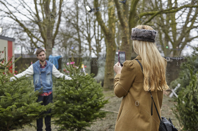 A woman shopping for a Christmas tree, assisted by staff