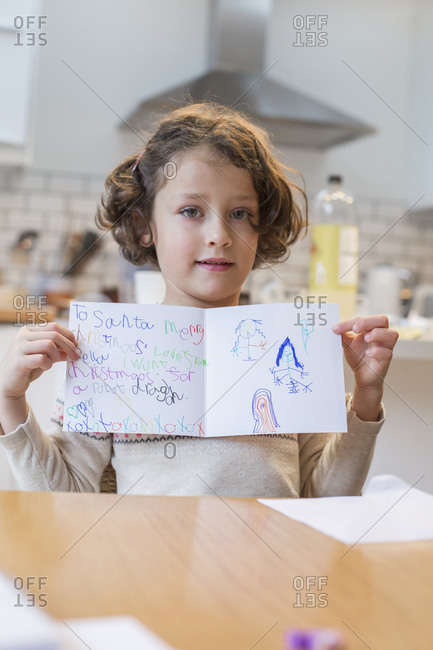 A girl showing her homemade Christmas card, a letter to Santa Claus, with drawings and writing