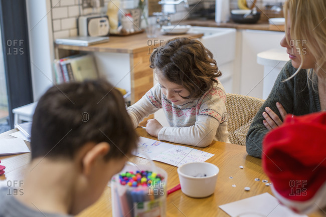 Three children and an adult woman at a table, drawing and writing cards and letters to Santa