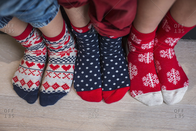 Three pairs of children's feet in bright patterned Christmas socks