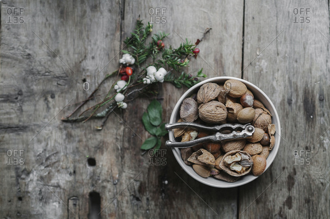 A dish of nuts and a nut cracker on a table with a sprig of yew wit red berries