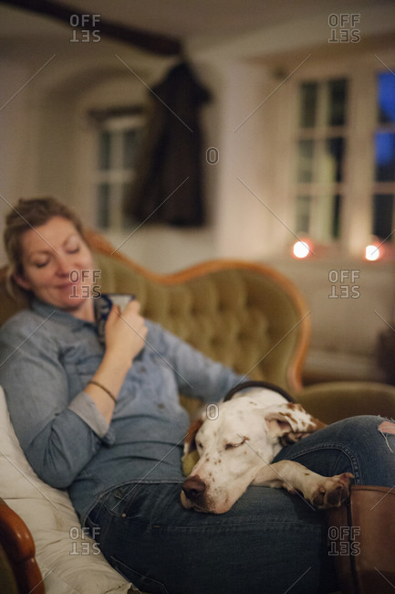A woman seated on a sofa with a large dog with his head on her lap