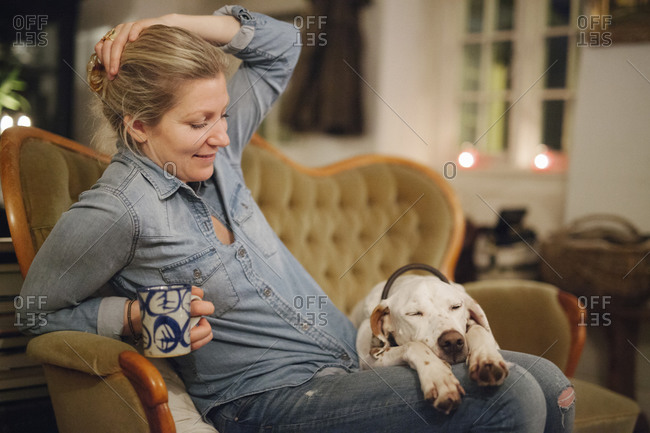 A woman seated on a sofa with a dog with his head on her lap