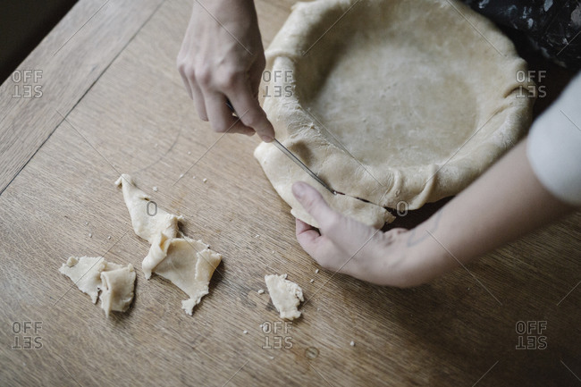 A woman trimming raw pastry dough to line a pie dish