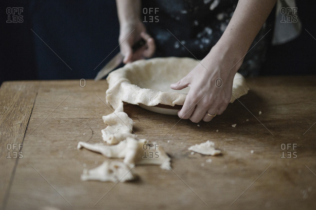 A woman trimming pastry dough to line a pie dish