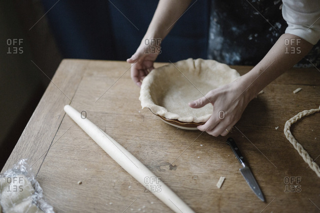 A woman working smoothing the edge of a pastry crust lining a pie dish