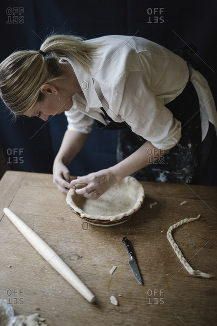 A woman working finishing the edge of a pastry crust lining a pie dish