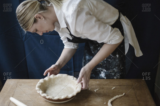 A woman working smoothing the edge of a pastry case lining a pie dish