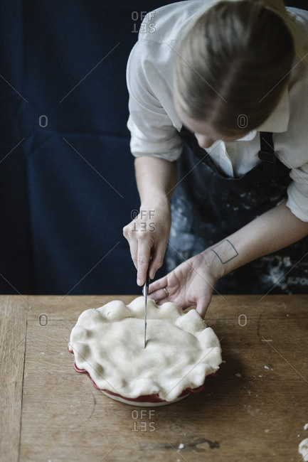 A woman cutting vent into top crust of raw pie