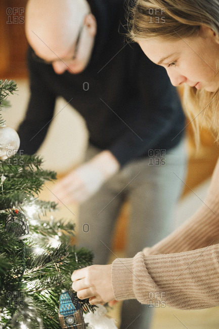 A father and daughter decorating a Christmas tree