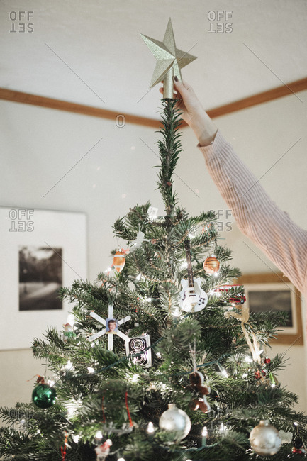 A person decorating a Christmas tree at home
