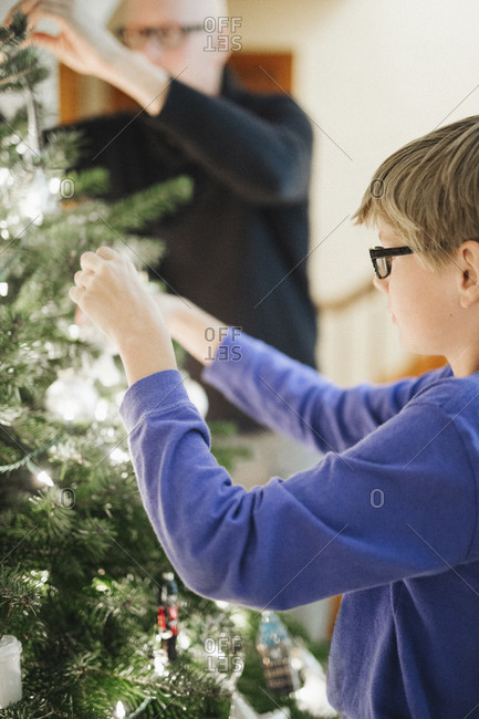 A boy decorating a Christmas tree at home
