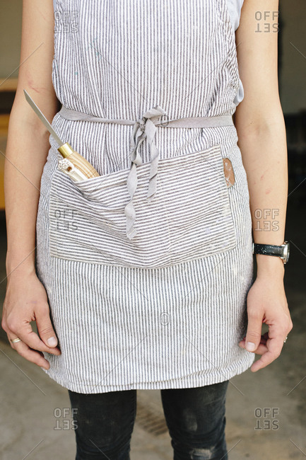 A woman in a workshop wearing a blue cotton apron with a chisel in the pocket