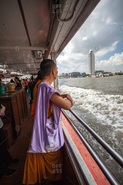 A monk overlooks the Chao Phraya River while onboard a river ferry in Bangkok, Thailand