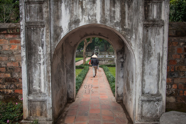 A visitor to the Temple of Literature in Hanoi, Vietnam, walks along a pathway