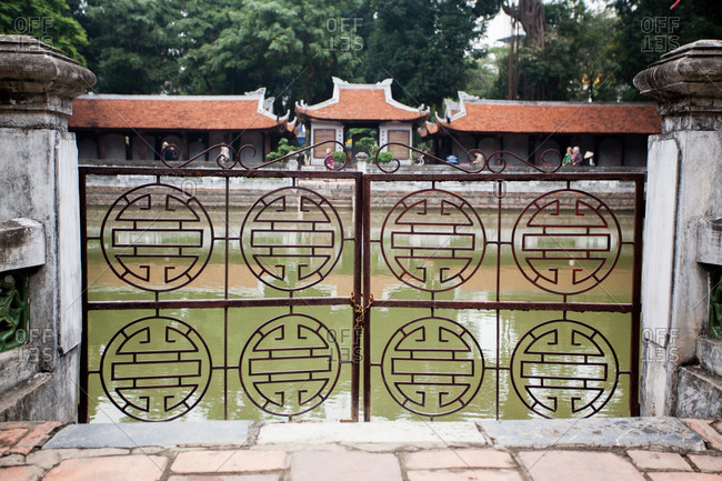 Ornate wrought iron gate surrounding a water feature at the Temple of Literature in Hanoi, Vietnam