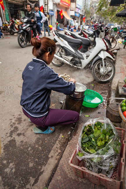 Hanoi, Vietnam - January 19, 2016: Woman preparing a meal of boiled eggs is prepared on the street