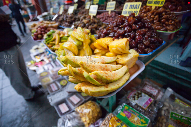 Samples of flavored and seasoned fruit and nuts at a street-side food stand in Hanoi, Vietnam