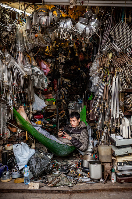 Hanoi, Vietnam - January 19, 2016: A junk dealer takes a break in his hammock to read his tablet  in a commercial district