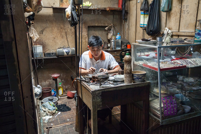Phnom Penh, Cambodia - January 22, 2016: A jewelry maker sits in his stall at the Russian Market