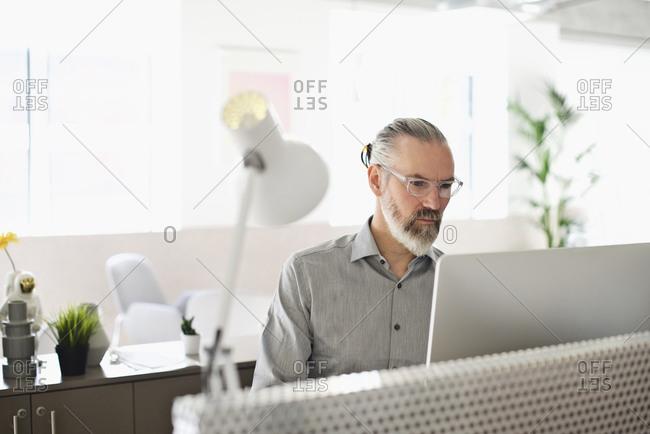 Man sitting in a bright, modern office using a desktop computer