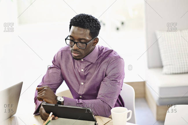 Man sitting in a bright, modern office looking at a digital tablet