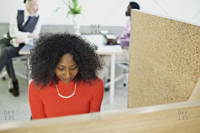Woman sitting in an office cubicle working