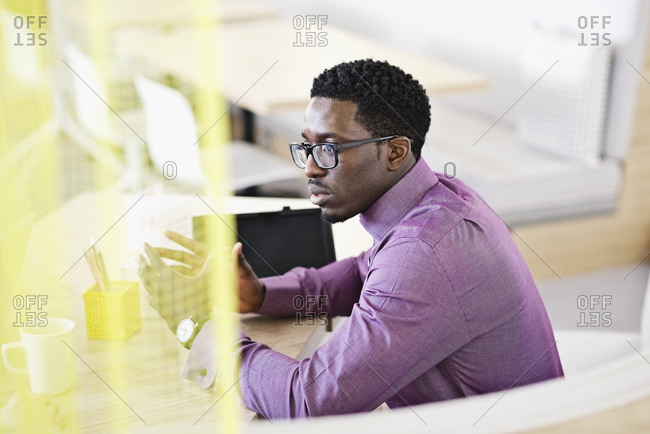 Man sitting in a bright, modern office talking with a co-worker