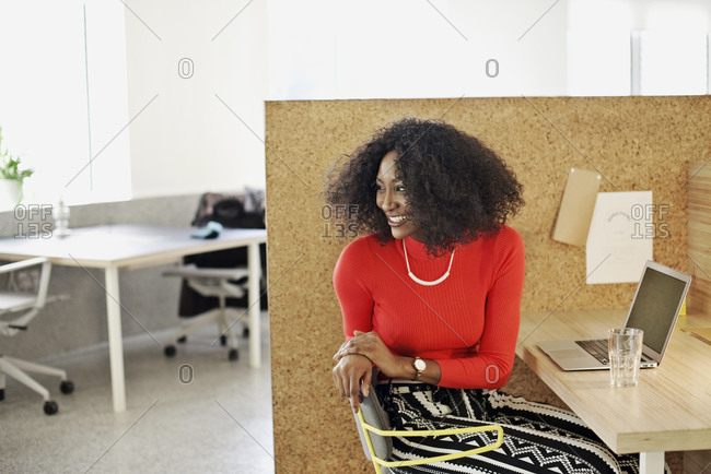 Woman in an office cubicle turned in her chair and smiling at a co-worker