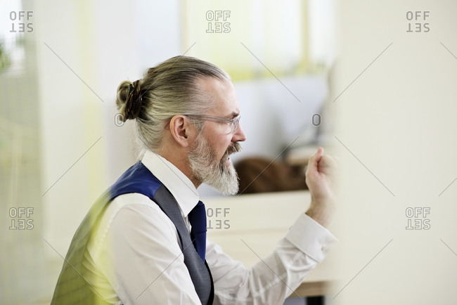Man sitting in an office talking to a co-worker