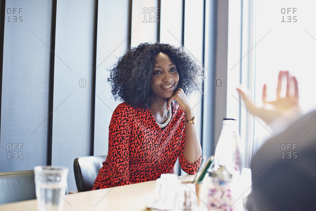 Woman sitting in a bright, modern conference room listening to a co-worker