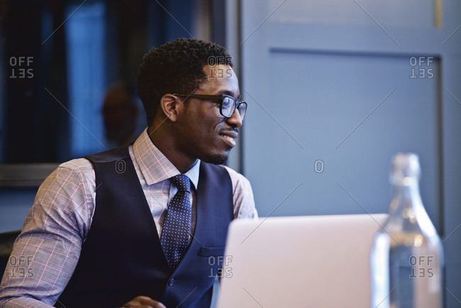 Man sitting in a bright, modern conference room listening to a co-worker