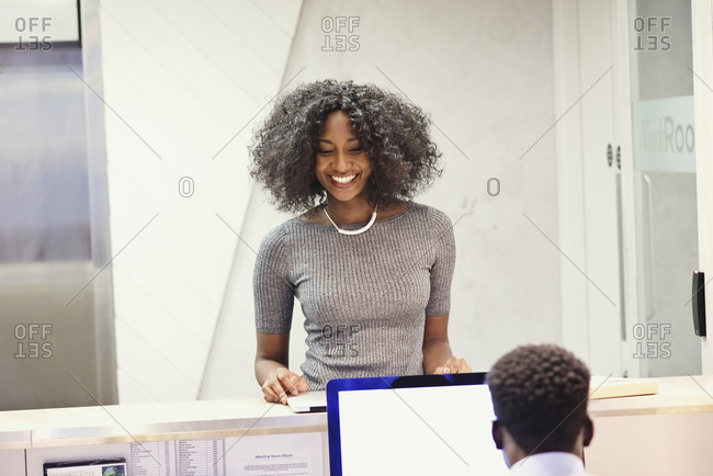Woman visiting a co-worker at the reception desk in an office
